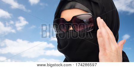 accessory, fashion and people concept - close up of muslim woman in hijab and sunglasses over blue sky and clouds background