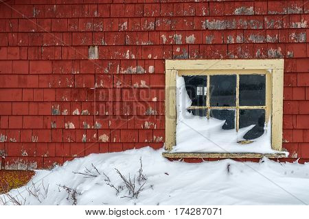 A window in an old weathered barn in winter.