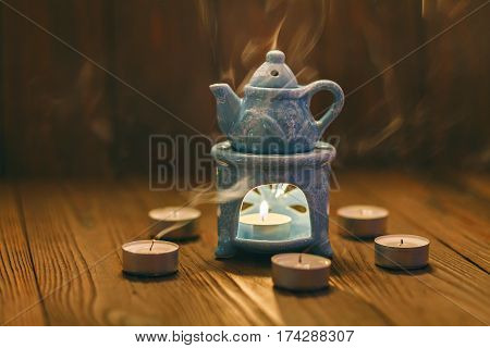The small blue oil warmer with the candle inside placed on a wooden surface.