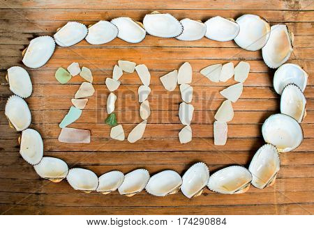 The inscription of glass and seashells on wooden background. Rustic seaside decor or wallpaper. Tropical seaside New Year celebration. 2017 year grungy banner template.