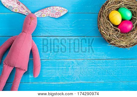 Easter background with eggs in nest and toy bunny on blue wooden background. Top view with copy space. Happy Easter card