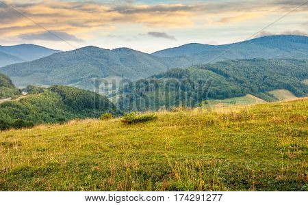 Grassy Meadow In Mountains At Sunrise
