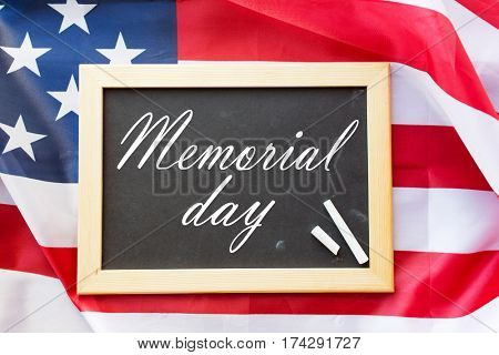 patriotism and national holidays concept - memorial day words on chalkboard, chalk and american flag