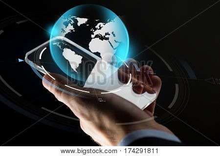 business, mass media, people and future technology concept - close up of businessman hand with transparent smartphone and virtual earth hologram over black background