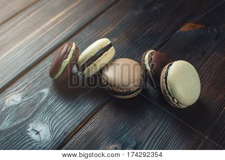 Coffee And Chocolate Macarons On A Dark Wooden Table