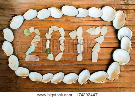 Sea shells and glass inscription 2017 on wooden background. Rustic seaside decor or wallpaper. Tropical seaside New Year celebration. 2017 year grungy banner template. Greeting card from exotic island