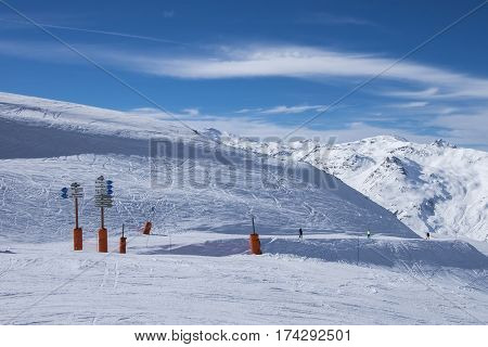 A wide piste, with signposts, highlighting the name of the piste and the direction of the piste, on a clear sunny day in Meribel, in the French Alps