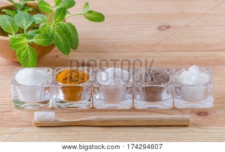 alternative natural toothpaste xylitol- soda turmeric - curcuma himalayan salt clay- ash coconut oil and wood toothbrush mint on wooden background poster
