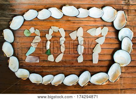 Seashore glass inscription 2017 on wooden background. Shells and glass vintage seaside decor. Tropical seaside New Year celebration. 2017 year grungy banner template. Greeting card from exotic island
