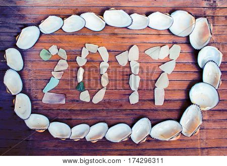 Beach glass inscription 2017 on wooden background. Shells and glass shabby seaside decor. Tropical seaside New Year celebration. 2017 year grungy banner template. Greeting card from exotic island