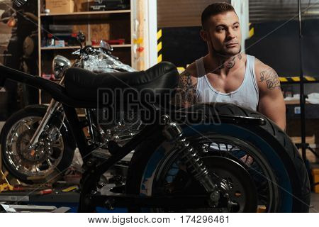 Deep in thoughts. Handsome muscular male person wearing jeans and white T-shirt being keen on tattoo sitting behind the motorbike