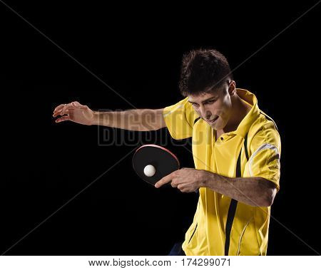 young sports man tennis-player in play on black background
