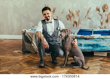 happy man with a dog in a gray suit smiling. Weimar pointer
