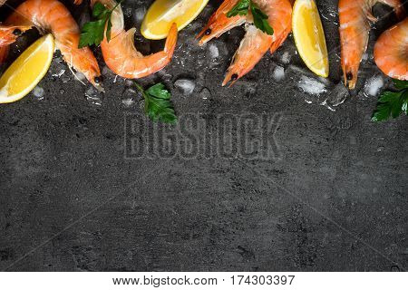 Prawns Shrimps with lemon in ice on slate background. Top view copy space. Food background.