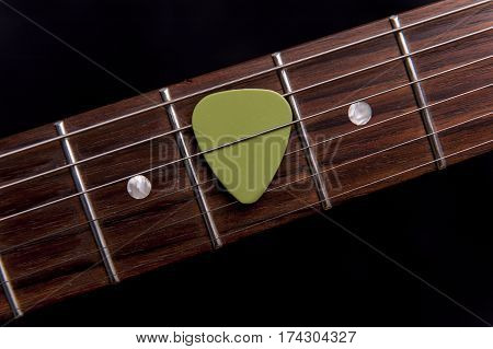 Green guitar pick on the fingerboard on black background