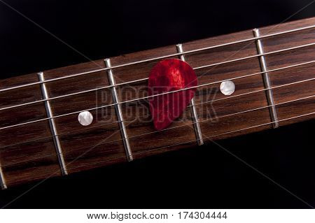 Red guitar pick on the fingerboard on black background