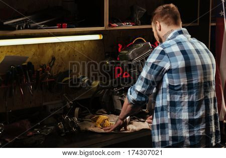 Let think. Infatuated boy standing near the table with tools wearing checked shirt putting his hands on the rag