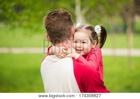 Closeup portrait of happy family. Little funny girl of 4 years age hugging her daddy in spring city park over green trees and grass background. Horizontal color photography