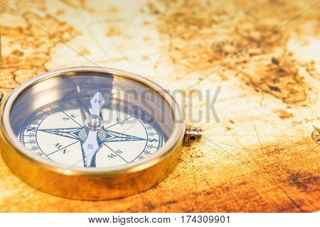 Old paper map with an ancient compass on it. Vintage travel background