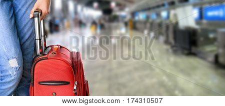 Woman holds suitcase in hands on the airport.