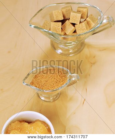 Assortment of sugar: brown cane sugar on the slices and brown sugar in containers and honey , on a light background, top view