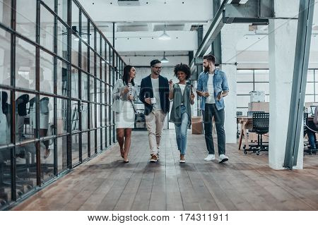 Ensuring success by working as a team. Full length of young modern people in smart casual wear having a discussion while walking through the office corridor