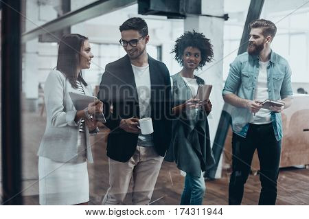 Working beyond the boarders of a desk. Group of young people in smart casual wear talking and smiling while walking together behind the glass wall in the creative office