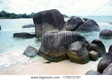 Natural rock formation in the sea and on a white sand beach in Belitung Island in the afternoon, Indonesia