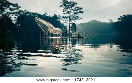 Fisherman casting out his fishing net in the river by throwing it into the air early in the blue colored morning to catch fish working with his fishing partner who is steering the little fishing boat.
