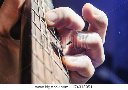The fingers of the musician on the guitar strings on the fretboard close up macro. Guitarist playing a chord on an instrument.