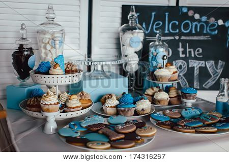 The variety of white and blue muffins and cookies on a stand. Horizontal indoors shot.