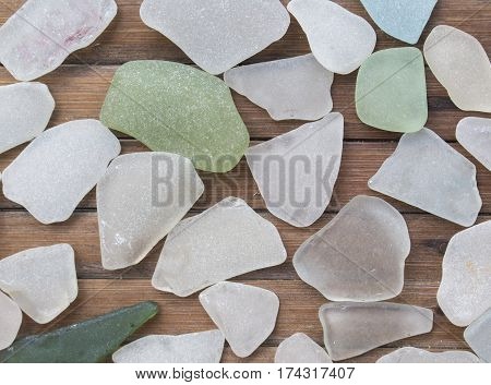 Smooth ocean glass on wooden background. Beach glass collection with white and green glass pieces. Glass pebbles mosaic on timber board. Grungy and shabby seaside decor. Seashore finding photo texture