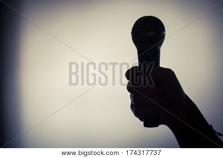 Close up shot of a silhouette of a hand holding a microphone.