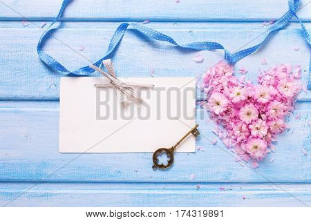 Background with heart from pink sakura flowers key and empty tag on blue wooden planks. Selective focus. Place for text.