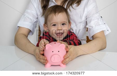 Little Child Is Putting Coins In Piggy Money Bank.
