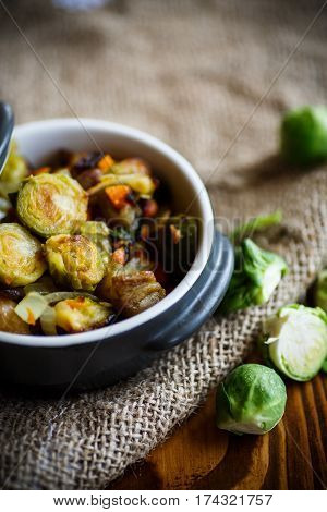 Brussels sprouts roasted with vegetables and beans in a ceramic form