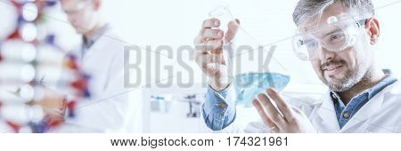 Chemist Looking At A Bottle With Chemical Substance