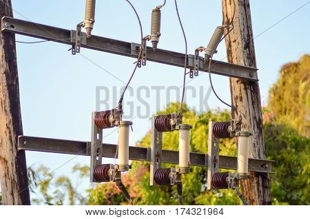 Cartridge fuses attach to a wooden pylon with insulators