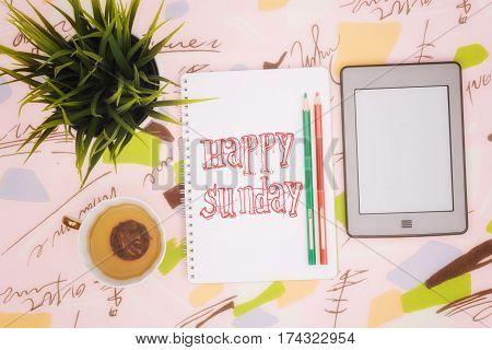 Tea cup, ebook and notebook with an inscription: happy sunday