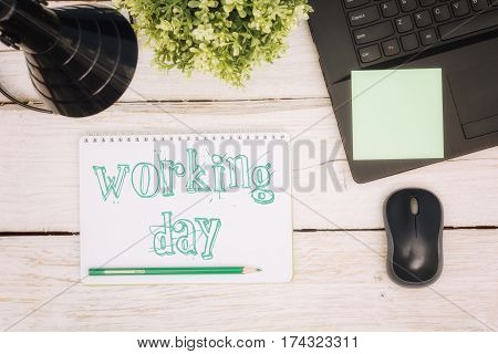 Workspace notebook and inscription in a scratchpad: working day