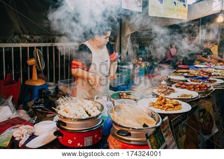 CHIANG MAI THAILAND - AUGUST 27 Thai woman cooks food for sale at the Saturday Night Market on August 27 2016 in Chiang Mai Thailand.