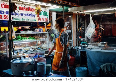 CHIANG MAI THAILAND - AUGUST 27: Food vendor waits for customers at the Saturday Night Market on August 27 2016 in Chiang Mai Thailand.