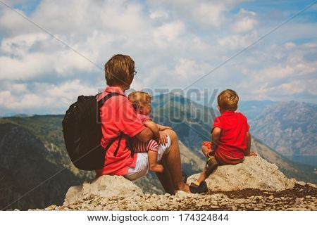 father with little son and daughter travel in scenic mountains