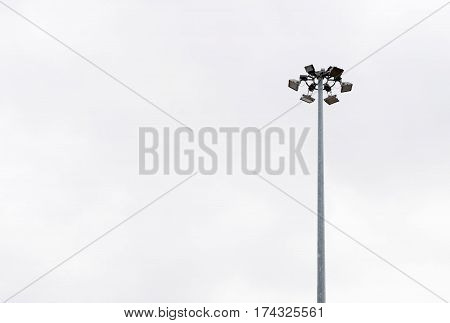 Lonely Stadium Light Or Lamp Post With Union Of Light Bulb Standing Alone With Clould And Blue Sky.