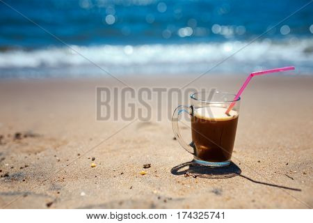 iced coffee latte on a beach ocean and seascape, shallow dof