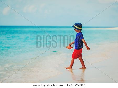 little boy playing with paper boat at tropical beach