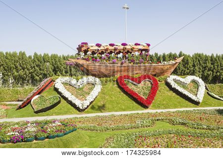 DUBAI UAE - NOV 27 2016: Hearts made of flowers and a historic arabian dhow ship at the Miracle Garden in Dubai. United Arab Emirates Middle East
