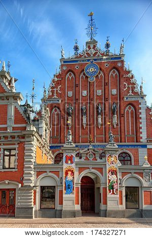 Historic House of the blackheads with sculptures and old clocks on the facade of the town hall square in Riga
