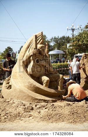 Khabarovsk Russia - August 30 2014: Sand sculpture festival - artists working on a man figure musician holding a guitar. Outdoor creative art competition