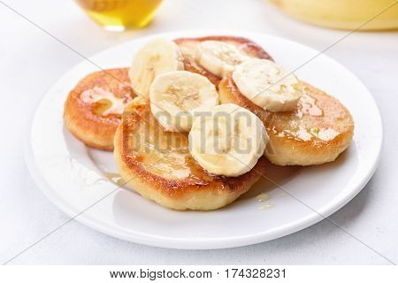 Fritters cottage cheese pancakes with banana slices close up view